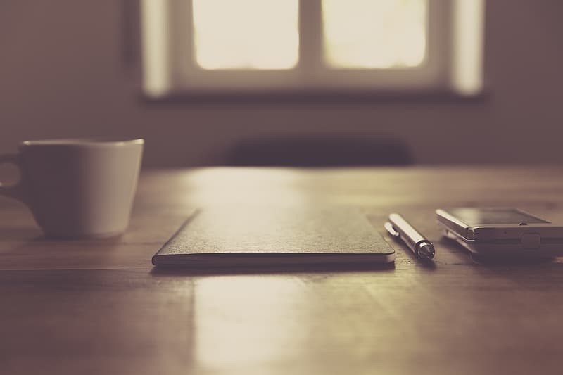 Selective focus photo of book and pen on wooden table near mug and smartphone