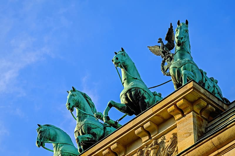 Three copper statue of horses on top of arch
