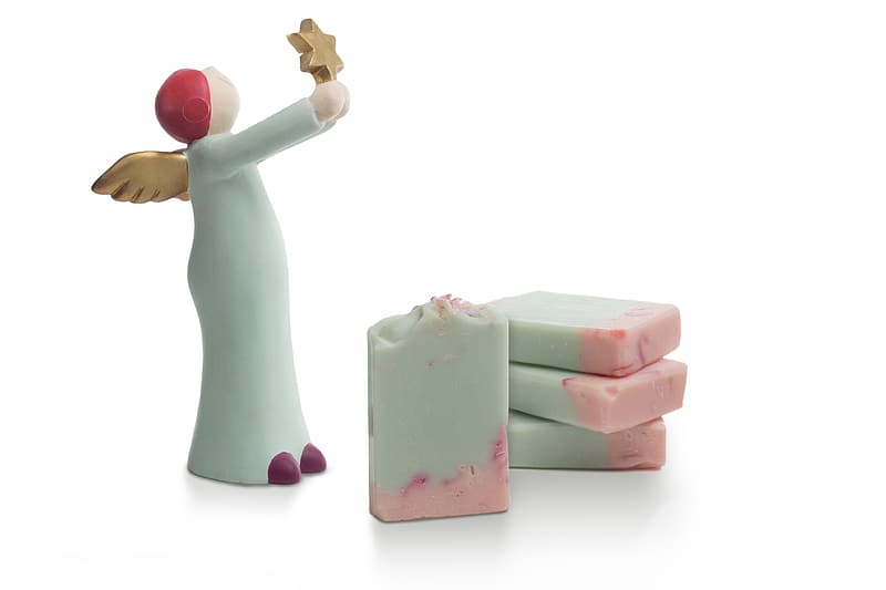 White ceramic figurine beside pink and white plastic toy