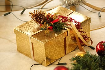Gold-colored floral gift box on beige surface