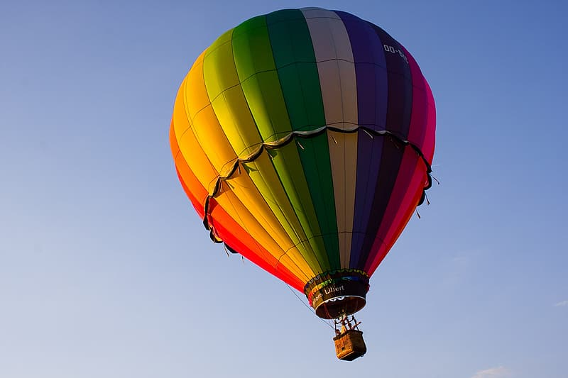 Blue, yellow, orange, and red hot-air balloon in flight