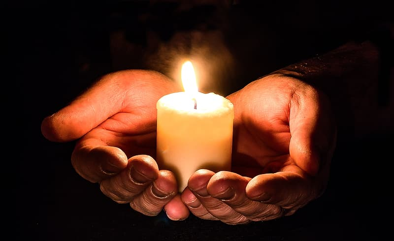 Person holding pillar of candle with two hands
