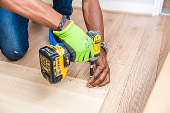 Man in green shirt holding black and yellow cordless hand drill
