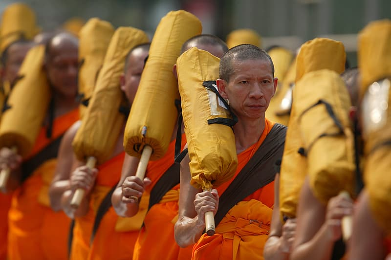 Monks holding yellow bags forming line