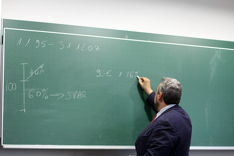 Man writing at chalkboard