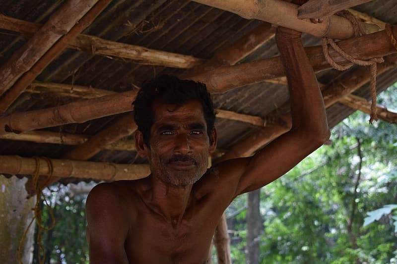 Topless man under brown wooden roof during daytime