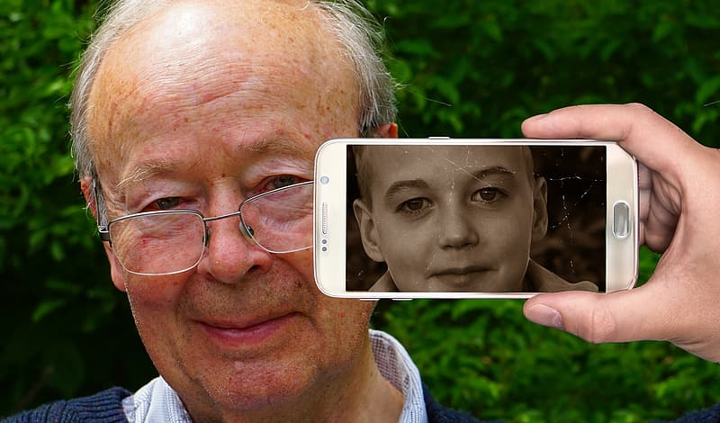 Person holding phone beside man with photo