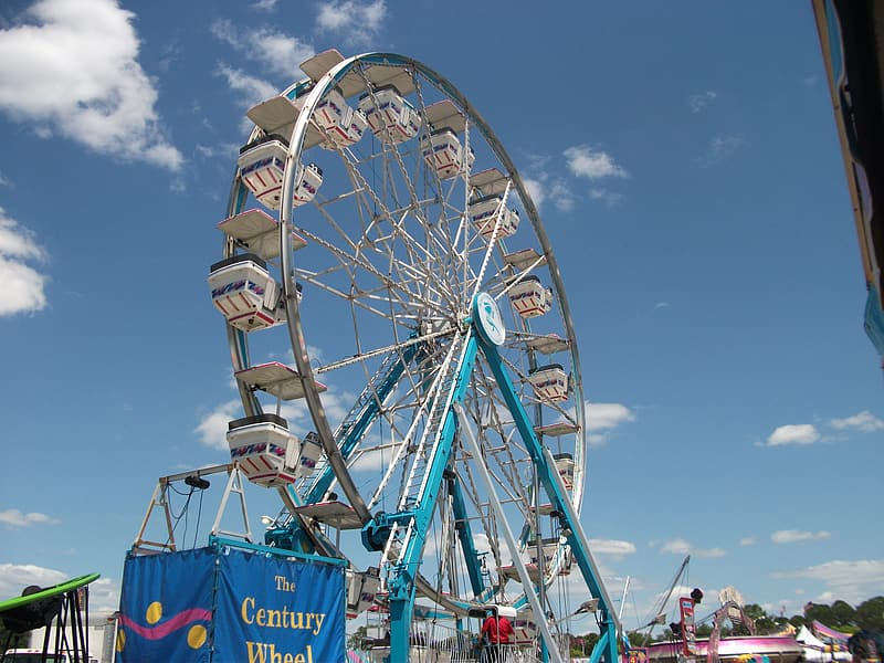 People riding on ferris wheel under blue sky during daytime