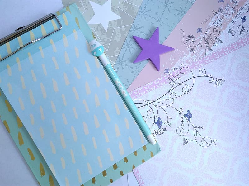 White and teal clipboard near teal pen