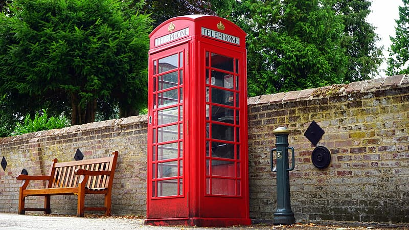 Red payphone near brown wooden bench