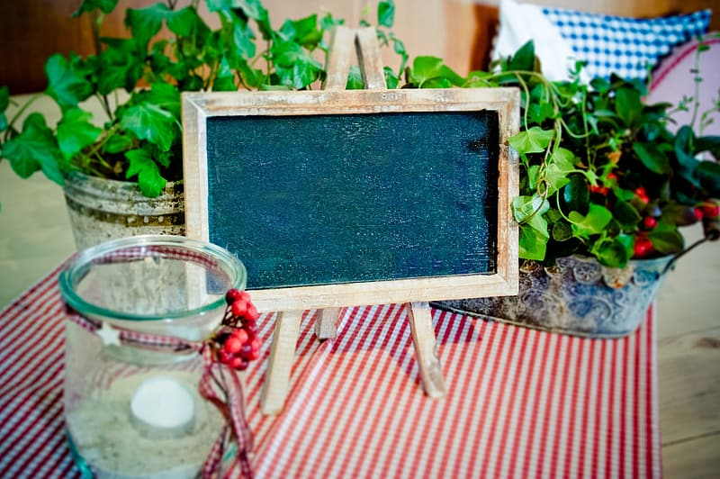 Clear brown wooden-framed chalkboard near black and white metal planters with green leafed plants