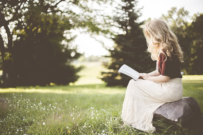Girl reading book as she sits on a rock