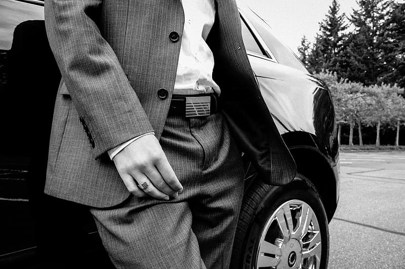Person in pinstripe suit jacket and dress pants standing beside car