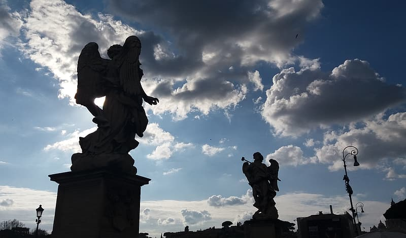Two angel statues under white clouds