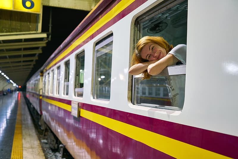 Woman in white shirt sitting on train