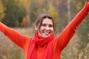 Photo of woman wearing orange sweater and red scarf