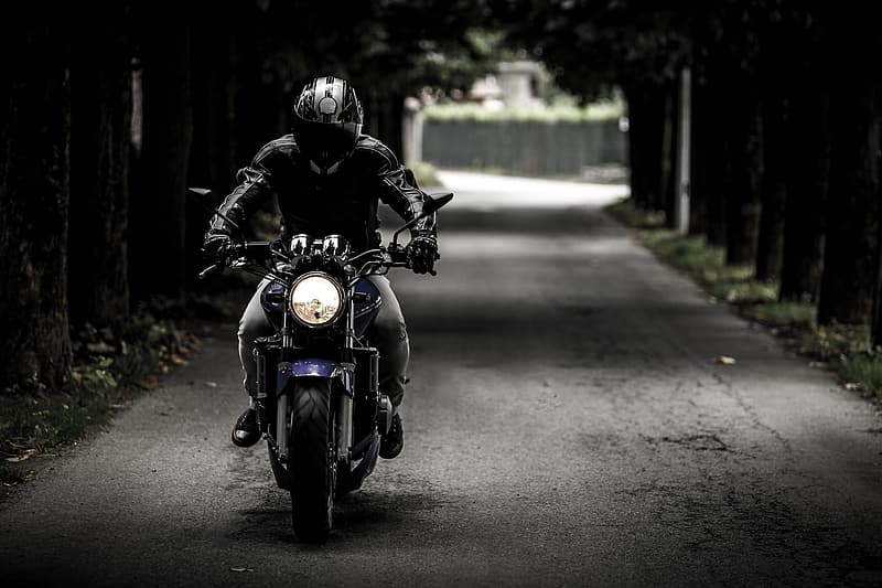 Grayscale photo of man in jacket riding motorcycle