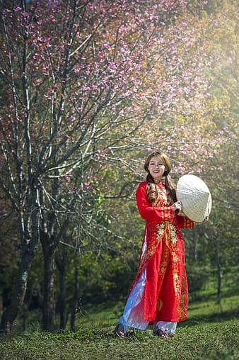 Woman wearing red traditional dress standing on grass fielkd