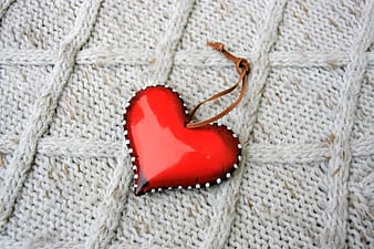 Red heart ornament on white knit textile