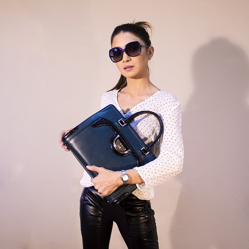 Woman wearing sunglasses, and white v-neck long-sleeved shirt while carrying bag