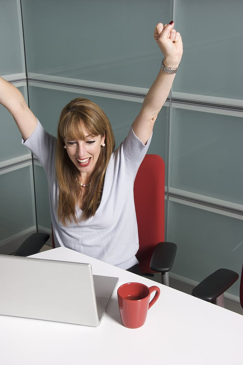 Woman sitting on office chair front of laptop raising hands