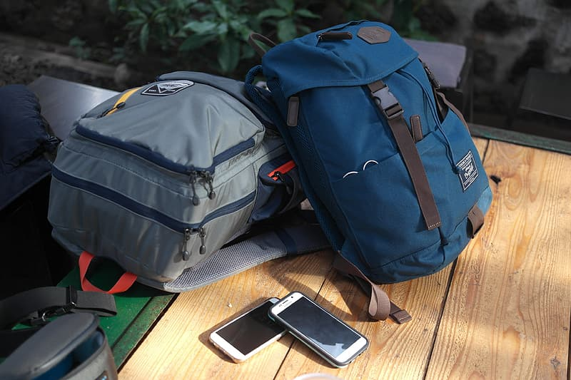 Black and gray backpack beside silver iphone 6 on brown wooden table