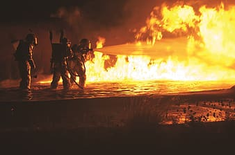 Three fire fighters holding water hose in front of flames