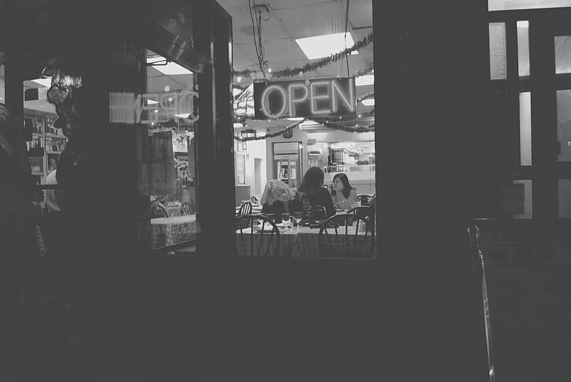 Grayscale photo of people sitting on chair near store