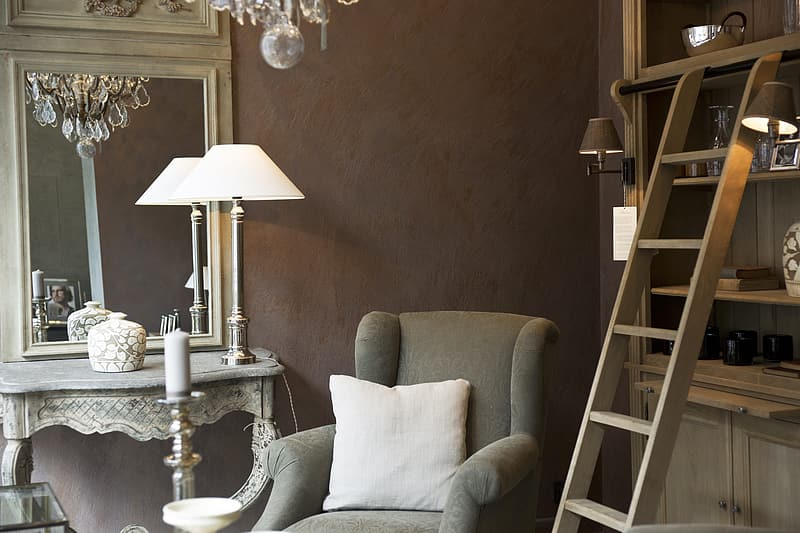 Gray sofa chair beside white table lamp and allder