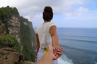 Woman in white t-shirt and yellow and black checkered shorts standing on cliff looking at on on near on