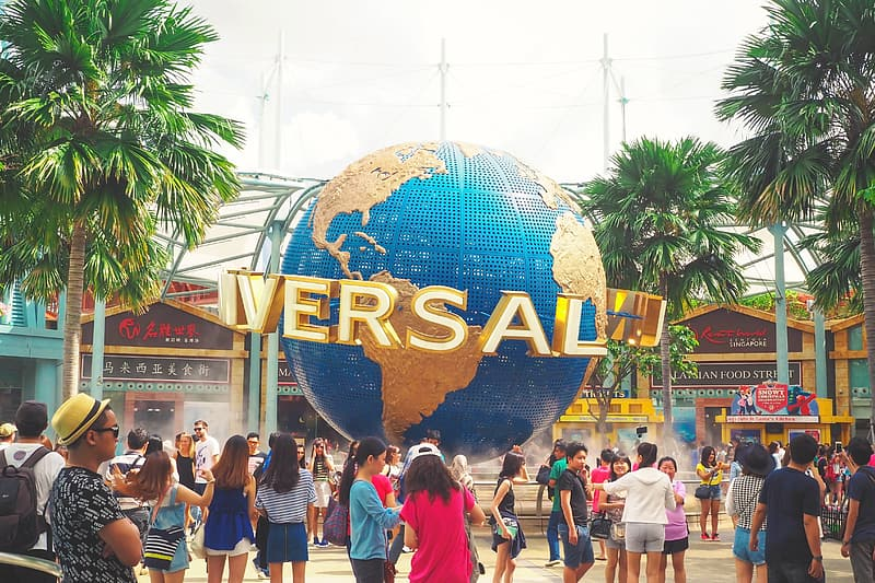 Group of people standing near Universal Studios building