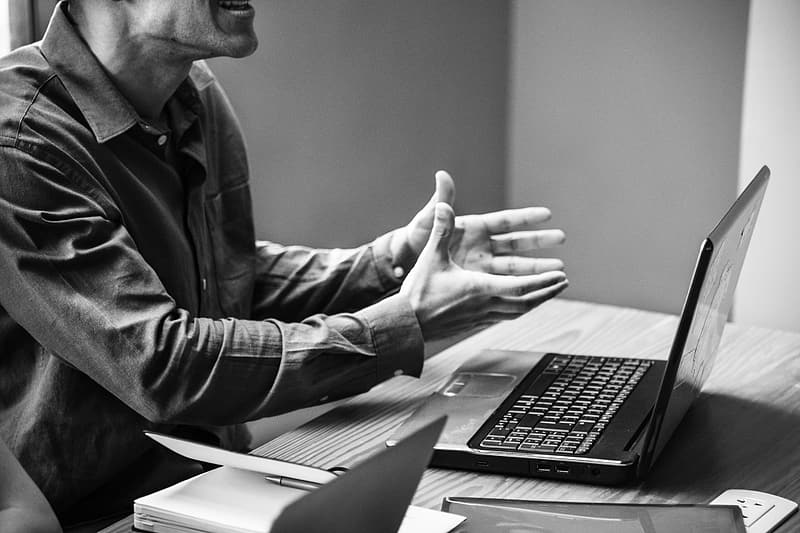 Grayscale photography of man sitting on chair infront of the laptop