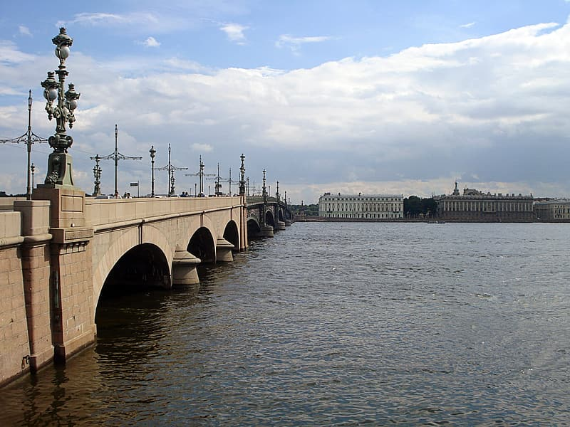 Brown concrete bridge over body of water during daytime