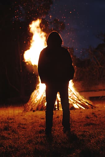 Silhouette of person standing in front of bonfire