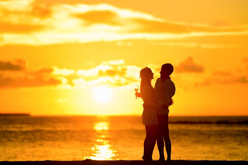 Silhouette of man and woman poses at golden hour