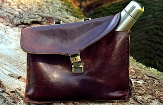 Gray stainless steel vacuum flask on brown leather bag on brown wood trunk at daytime