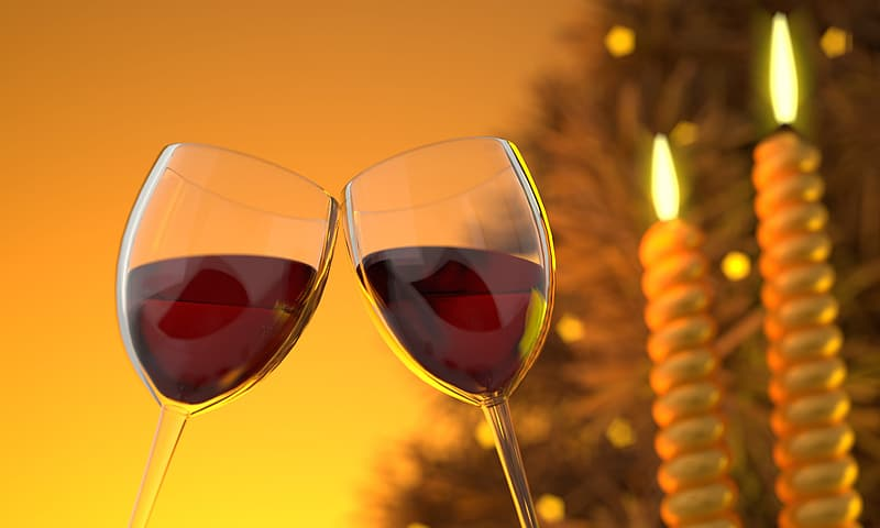Two clear wine glasses with red liquids near two white candle sticks in tilt shift photography