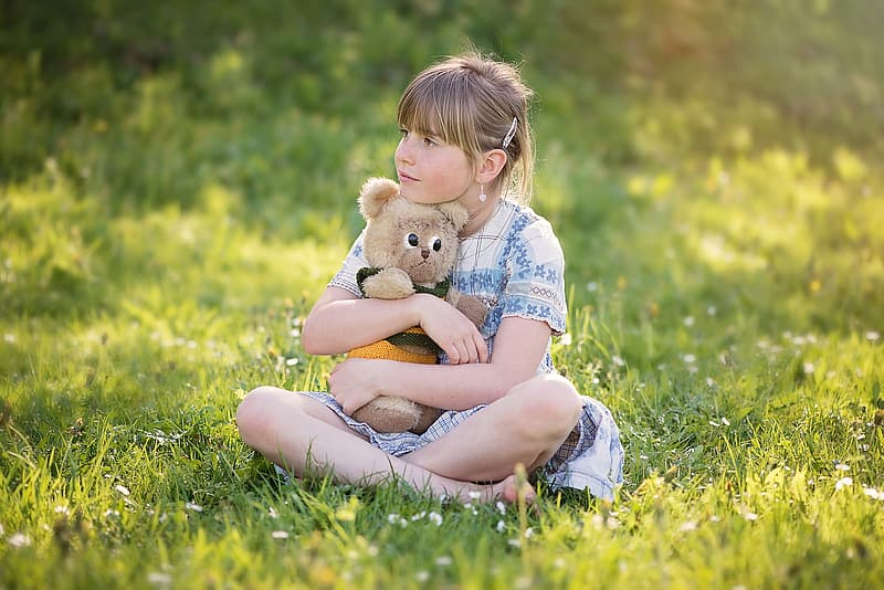 Girl hugging brown bear plush toy while sitting on grass field during daytime