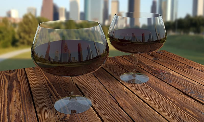 Two wine glasses filled with wine on table