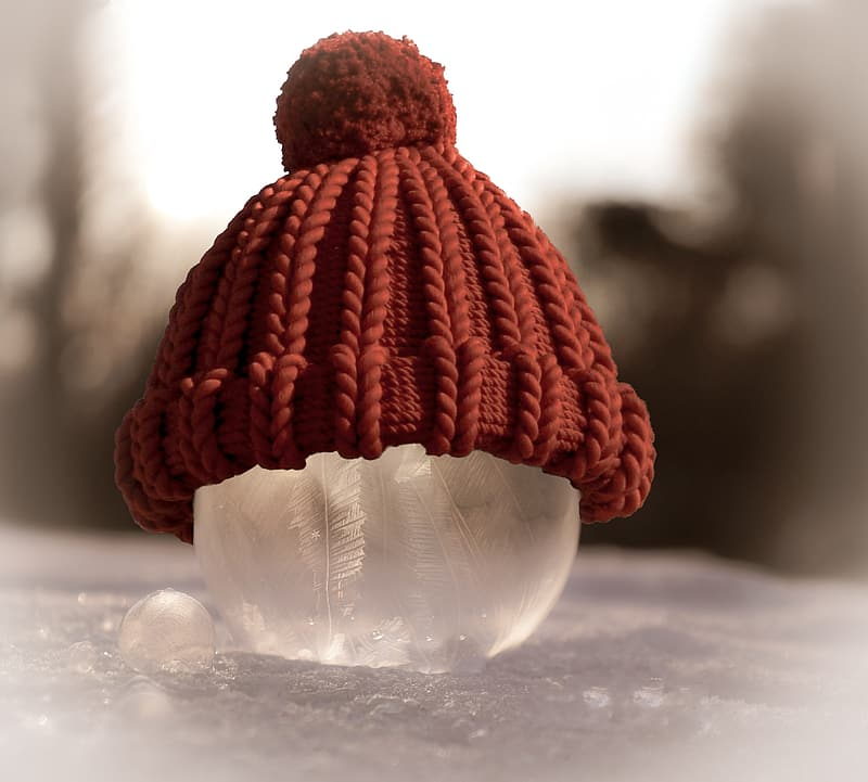 Red and white knit ball on white snow