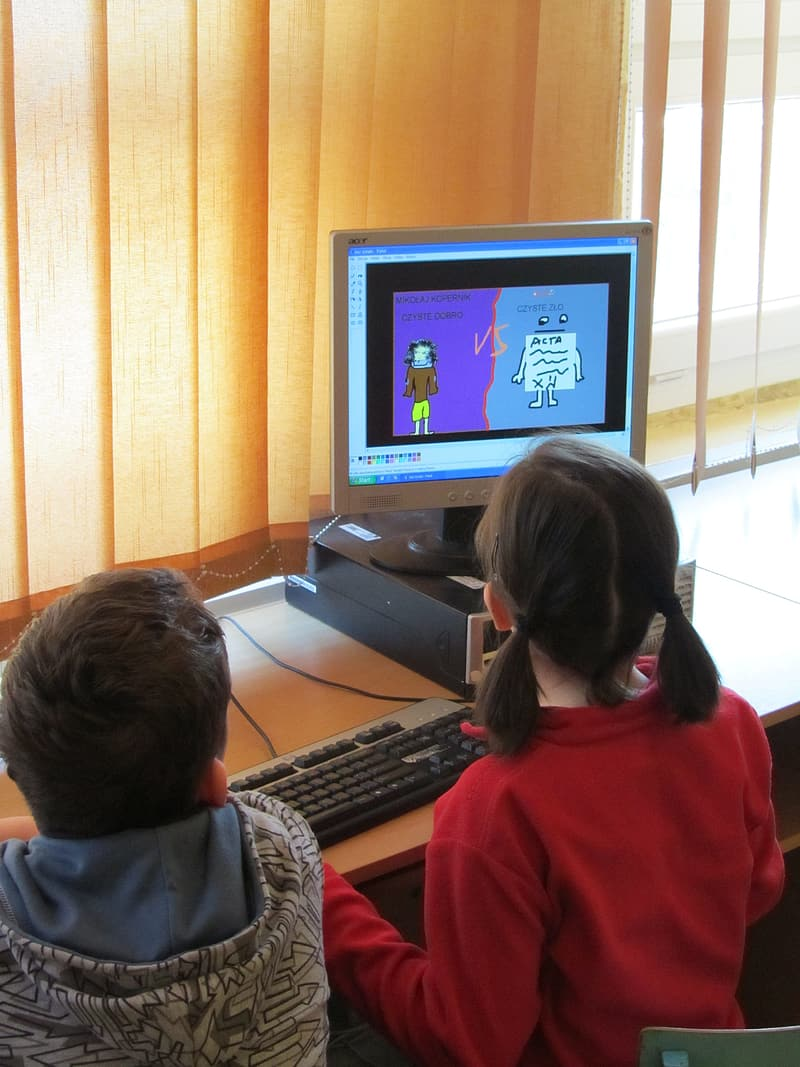Boy and girl using desktop computer in the room