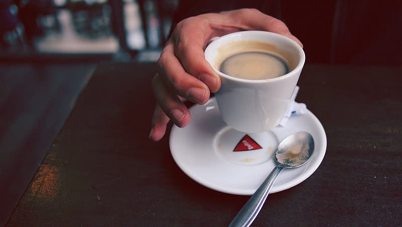 Person holding white ceramic cup with brown liquid