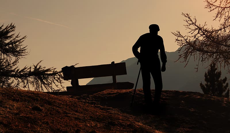 Silhouette of man standing beside bench during sunset