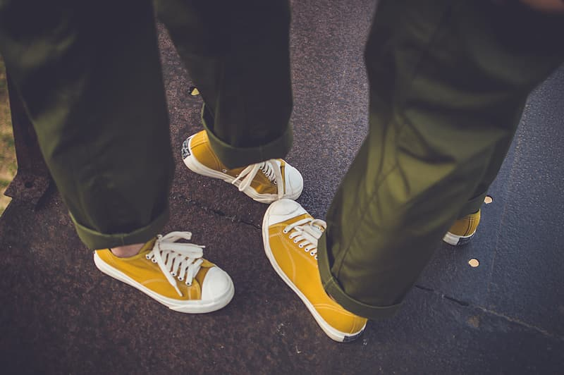 Person wearing yellow and white converse all star low top sneakers
