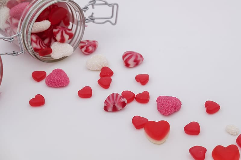 White and pink heart shaped candies on clear glass jar