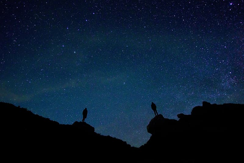 Two person standing on rock under starry night silhouette photograph
