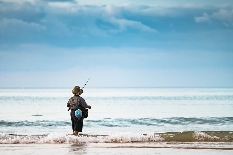 Person standing on seashore holding fishing rod