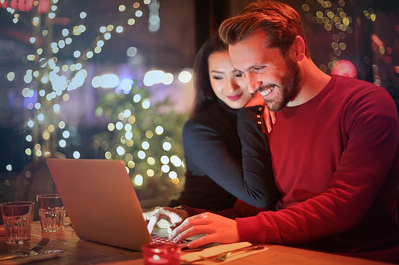 Young couple surfing on internet with laptop during romantic dinner in a restaurant