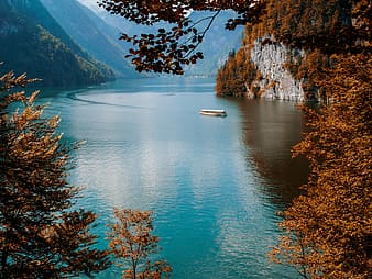 White boat on lake near trees and mountain during daytime
