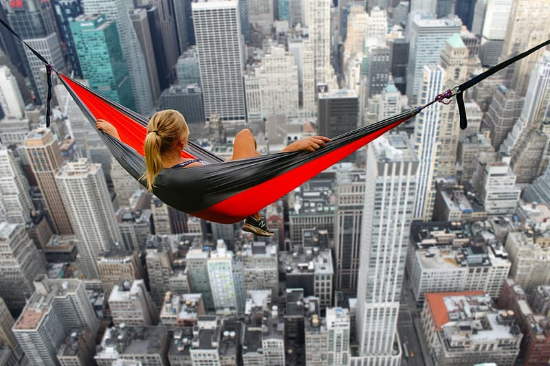 Woman sitting on and red hammock overlooking high-rise buildings